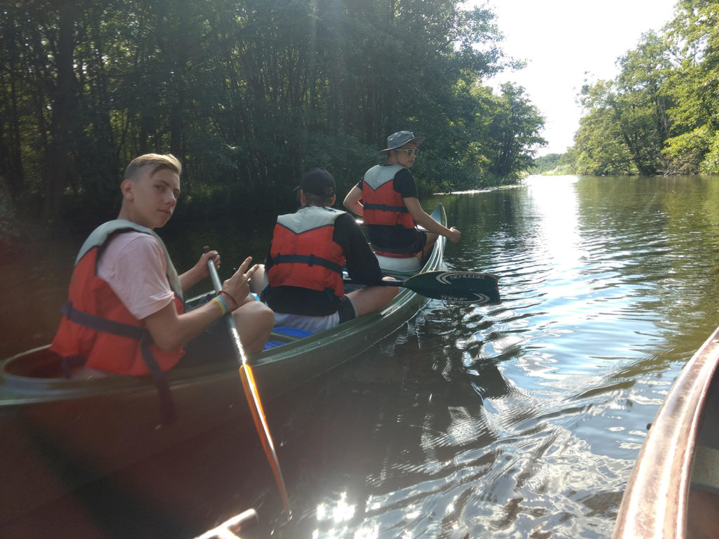 Jugendliche mit Schwimmwesten sitzen in einem Kanu auf einem Fluß.
